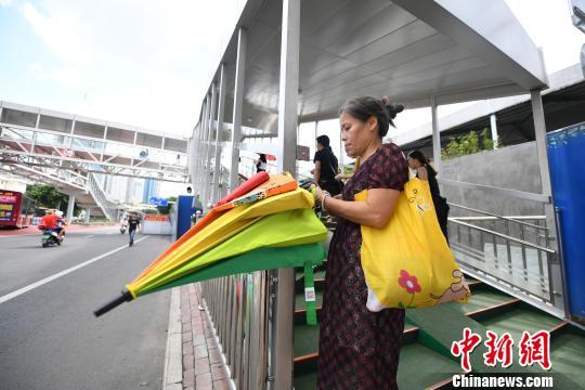 图为一市民尝试取用共享雨伞。 俞靖 摄