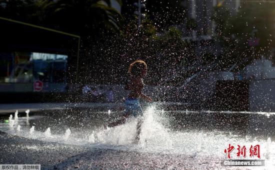 当地时间2017年7月6日,美国加州洛杉矶,儿童在喷泉戏水解暑。