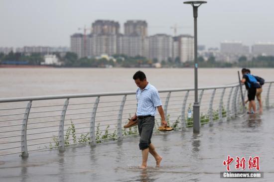 7月7日,市民从长江南京下关段被淹的滨江步道上经过。当日,江苏省防汛防旱指挥部办公室发布的信息显示,受长江上中游来水影响,南京站潮位上涨,超警戒水位。记者 泱波 摄