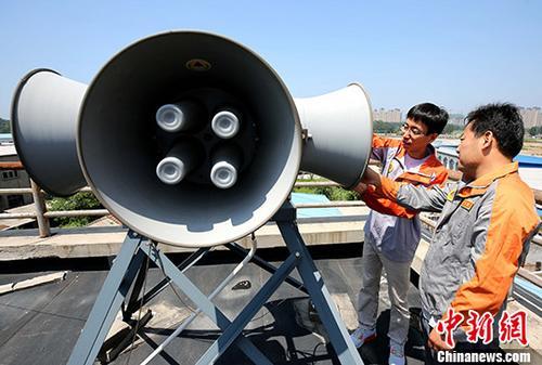 图为工作人员对一处扩音设备进行调试。 发 刘亮 摄
