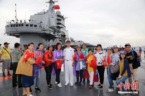 香港市民在辽宁舰飞行甲板与官兵合影。 记者 李唐 摄