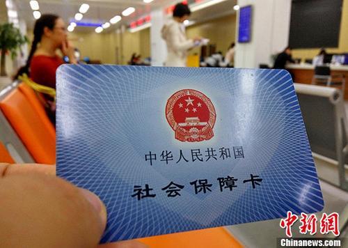 图为福州市市民服务中心前来办理社保业务的民众展示自己的社会保障卡。(资料图片)中新社记者 张斌 摄