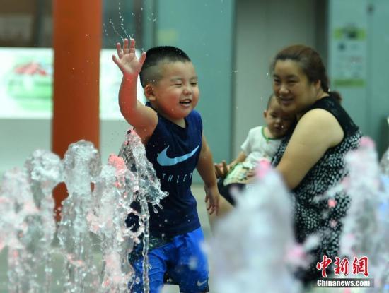 7月11日,河北石家庄一喷水景观处,孩童玩水纳凉。中新社记者 翟羽佳 摄