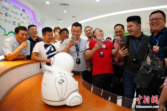 7月11日,华裔杰出青年代表与智能机器人互动。近日,由中国国务院侨务办公室和中国海外交流协会举办的第十一届世界华裔杰出青年华夏行北京线活动启动。来自30个国家和地区(含港澳)的近90名华裔杰出青年代表赴天安门城楼、故宫、前门、长城等地参观考察。中新社记者 韩海丹 摄