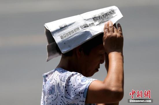7月11日,民众在烈日下出行。当日,陕西省气象台升级发布高温红色预警信号,未来24小时陕西大部分地区将出现37℃以上高温天气,局部地区将达40℃以上,未来四天还将会出现今年以来最强高温天气。 中新社记者 张远 摄