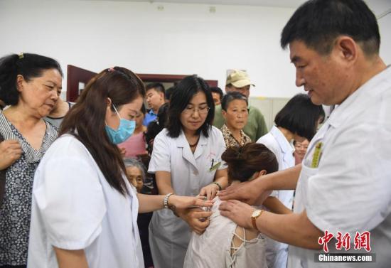 """资料图:济南中医院为患者贴""""三伏贴""""。 中新社记者 张勇 摄"""