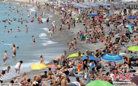 来尼斯海边度假的游客遍布沙滩。
