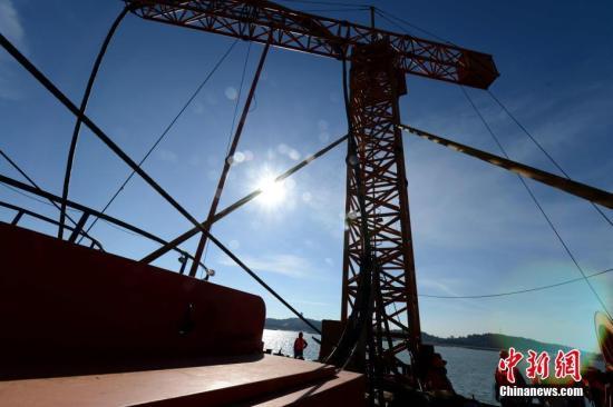 """7月12日,福建莆田忠田村至""""妈祖故乡""""湄洲岛110千伏海底电缆线路在湄洲湾海域敷设成功。这条总长约3.43千米的海底电缆,是进入湄洲岛第一条110千伏海底输电线路,也是目前进入湄洲岛电压等级最高的海底电缆线路。该海底电缆的成功敷设标志着由福建送变电公司负责施工的忠田-湄洲110千伏线路工程""""海陆空""""全线贯通,为岛上3.8万居民生活提供安全可靠的电力保障。图为福建送变电公司员工冒酷暑敷设海底电缆。 王东明 摄"""
