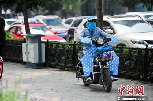 """7月12日,辽宁沈阳,市民""""全副武装""""在炎热的天气出行。 中新社记者 于海洋 摄"""