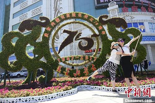 7月12日,民众在位于呼市商业区的花坛前自拍。 记者 刘文华 摄