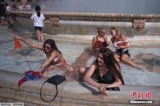 当地时间7月12日,西班牙塞维利亚持续高温,民众在西班牙广场上的喷泉池里泡澡降温。