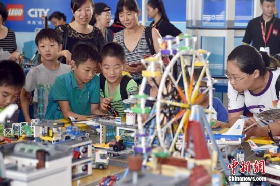 """7月13日上午,2017年第八届北京玩博会在全国农业展览馆开幕。本届玩博会由中国玩具和婴童用品协会与京东超市共同主办,汇集全球30多个国家和地区的200余个优质品牌,围绕""""智能、教育、IP""""三大主题,推出上百场亲子体验活动。与往届单纯线下体验不同,今年还将举办""""北京玩博会吉尼斯世界纪录挑战嘉年华、夺宝奇兵我的金币我做主、全家欢大舞台、成长照相馆、新科技玩具竞技""""等活动,力邀顶级育儿媒体《父母世界》专家亲临互动,让未能到场的亲子家庭也能体验玩具新玩法,线下线上互动打破时空局限。图为家长与小朋友在玩博会上互动体验玩具。 <a target='_blank' href='http://www.chinanews.com/' >中新网</a>记者 金硕 摄"""