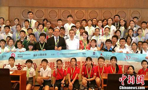 7月13日,2017《基本法》全港校际问答比赛学习团的百名香港小学生来到清华大学,参加全国人大常委会香港基本法委员会副主任张荣顺的讲座,并就香港基本法有关问题进行交流。图为学习团成员与张荣顺合影。 <a target='_blank' href='http://www.chinanews.com/'>中新社</a>记者 陈小愿 摄