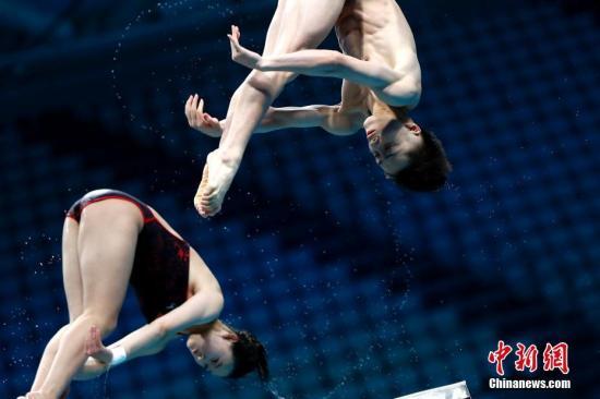 中国跳水队十米台混双组合连俊杰(右)、任茜进行赛前训练。 中新社记者 富田 摄