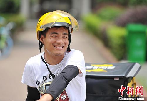 """7月14日,在有""""火炉""""之称的江西南昌,一位在高温酷暑下送外卖的送餐员。 中新社记者 刘占昆 摄"""