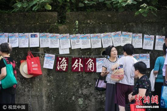 """资料图:2017年7月15日,杭州杭州每天最高气温都超过了35度,一条马路两边,吸引了数百名大伯大妈前来""""相亲"""",现场人山人海,却难觅年轻人的身影。 图片来源:视觉中国"""