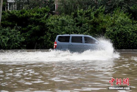 7月16日,长春迎来暴雨天气,市区多处出现内涝积水。图为车辆在水中行驶。 张瑶 摄