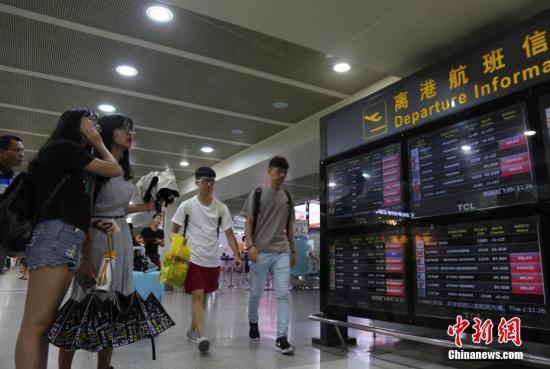 尹海明/资料图:乘客在三亚凤凰国际机场查看航班信息。中新社记者尹海...