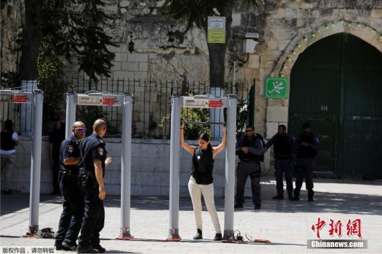 """当地时间2017年7月16日,耶路撒冷,以色列重新开放了阿克萨清真寺,但是巴勒斯坦穆斯林拒绝进入。以色列警方在通往圣殿山的入口以及阿克萨清真寺门口加装金属探测器,并将在该区域加设摄像头。负责管理阿克萨清真寺等宗教设施的伊斯兰宗教基金会以以色列警方此举导致""""现状发生改变""""为由,拒绝向警方开放阿克萨清真寺大门并要求穆斯林在以色列警方新增安保设施拆除前不要前往阿克萨清真寺。 7月14日,三名以色列警察在圣殿山外遭枪击,其中两人身亡。事发后,以色列警方封锁阿克萨清真寺,禁止穆斯林前往礼拜,并关闭耶路撒冷老城穆斯林区大部分商铺以及东耶路撒冷主要商业街店铺,封锁耶路撒冷老城附近交通。图为一名民众接受安检。"""