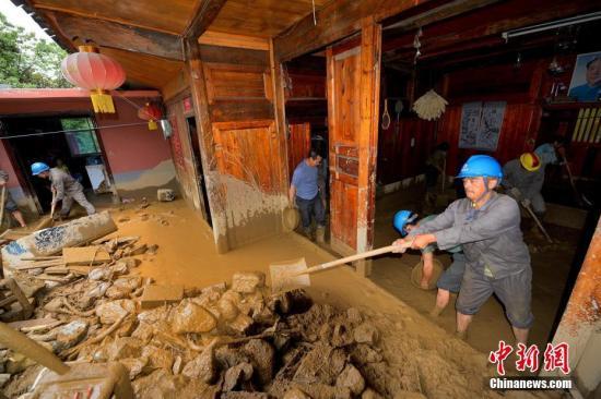 资料图:救援队帮助受灾户清除家中淤泥。雷勇 摄