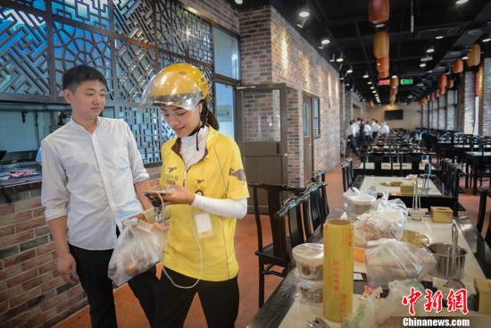 资料图:外卖送餐员取完餐,准备送往顾客处。中新网记者 富宇 摄