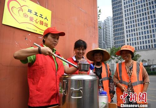 高温下志愿者为环卫工人提供绿豆汤。 中新社记者 韩苏原 摄