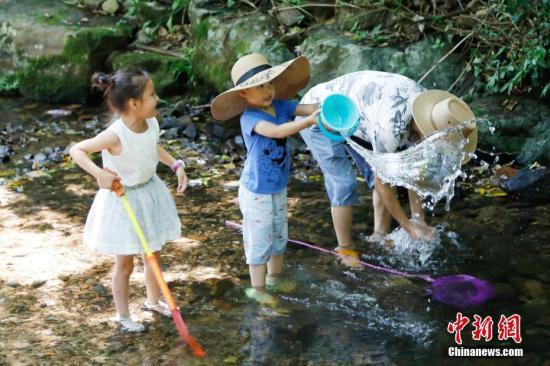 7月18日,小朋友们正在戏水。由于连日的高温,浙江杭州的市民与游客纷纷来到九溪十八涧,在溪流中戏水纳凉以躲避酷暑。中新社记者 王远 摄