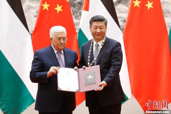 """7月18日,中国国家主席习近平在北京人民大会堂同巴勒斯坦国总统阿巴斯举行会谈。会谈后,阿巴斯授予习近平""""巴勒斯坦国最高勋章"""",以表达对中方支持巴正义事业的深切感谢和对习近平本人的崇高敬意。中新社记者 杜洋 摄"""