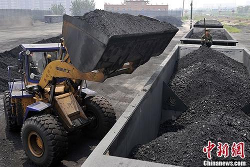 山西太原煤炭集运西站内,工人为火车车厢装煤作业。(资料图片) 中新社记者 韦亮 摄