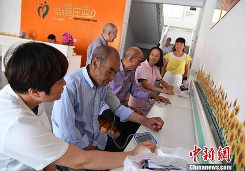 7月19日,来自福建省沙县高砂镇卫生院的医护人员为住在敬老院的老人进行体检。随着小吃业的发展,沙县大量青壮年劳力外流,全县26万人口中6万人在外经营小吃,占该县农村人口的60%,农村老年人养老困难成了一个大问题。为了应对农村人口老龄化,创新探索乡村养老新模式,由镇政府与企业合作建设,引进第三方管理机构运营的沙县高砂镇敬老院7月正式投入运营,目前已有27位老人入住,享受着专业的护理。中新社记者 张斌 摄