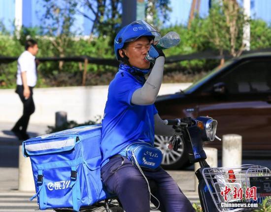 7月20日,武汉高温持续,送外卖的小哥喝水降温。中新社记者 张畅 摄