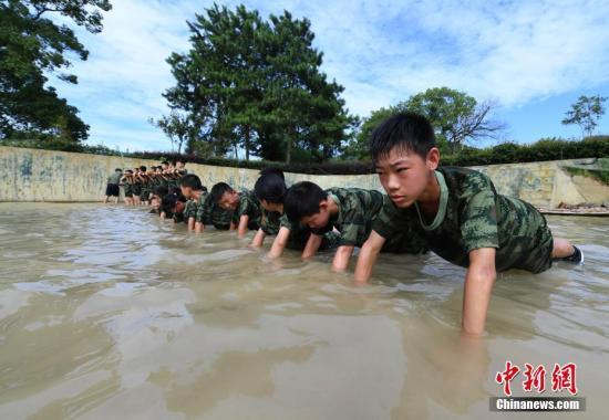 """暑假期间,中国众多中小学生选择参加模拟军事拓展类的夏令营,孩子们在教官和老师带领下通过参加一系列训练锻炼体魄、磨炼意志,增强团队和感恩意识,体验不一样的""""特种兵""""式暑假生活。赵春亮 摄"""