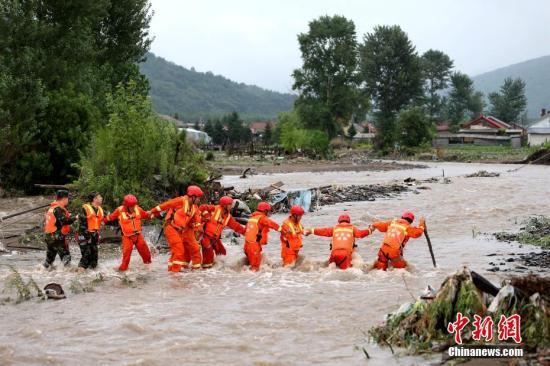 救援人员手牵手通过急流区域。文/王舒 解培华 图/王舒