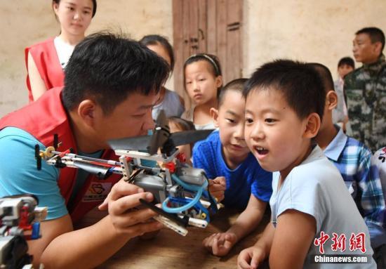 资料图:志愿者在向孩子们讲解机器人工作原理。 周亮 摄