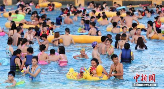 7月19日,游客在武汉市一水上公园戏水纳凉。近日,湖北省武汉市持续高温天气,不少市民外出戏水纳凉,体验水上乐园推出的趣味活动。中新社记者 张畅 摄
