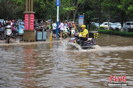 资料图:外卖小哥骑电动车涉水送餐。中新社记者 刘冉阳 摄
