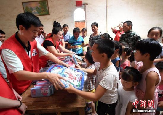 材料图:意愿者背留守女童赠予书包、文具盒。 周 摄