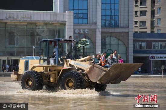 7月19日至20日,吉林省永吉、蛟河等13个县(市、区)出现强降水,降水导致吉林市城区部分区域发生严重内涝。目前,各部门正加紧进行抢险、转移、安置等工作。图为7月21日早晨,吉林,路面的积水给出行的市发带来不便。孙鑫 摄 图片来源:视觉中国