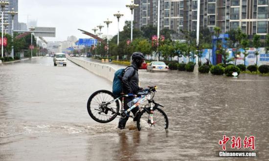 7月22日,民众抬着自行车从积水路上走过。当日,昆明持续降雨,城区多处路段积水。昆明市气象台发布暴雨蓝色预警,未来12小时昆明市区及周边多地区将持续降雨。 中新社记者 任东 摄