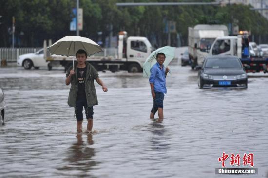 资料图:7月22日,驾驶员雨中寻找遗落在水里的车牌。当日,昆明持续降雨,城区多处路段积水。昆明市气象台发布暴雨蓝色预警,未来12小时昆明市区及周边多地区将持续降雨。 中新社记者 任东 摄