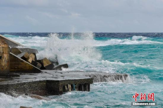 资料图:受台风桑卡影响,23日西沙、中沙群岛附近海面,西到西南风7-8级,阵风9级,三沙永兴岛附近海面掀起层层巨浪,拍打岸边。 中新社记者 骆云飞 摄