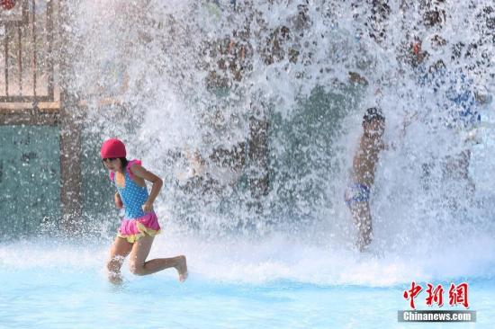 7月23日,两名孩子在南京欢乐水魔方内戏水。当日,南京市气象台将高温橙色预警信号升级为高温红色预警信号。 中新社记者 泱波 摄