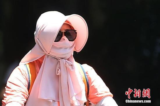"""7月23日,南京户外高温逼人,用温度计测量的中午实时温度超过40摄氏度。图为""""全副武装""""的民众。泱波 摄"""