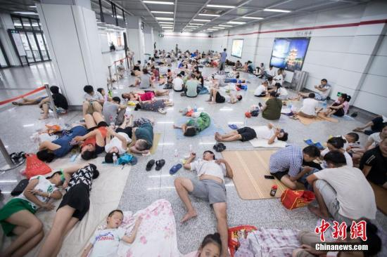 """在杭州一地铁站内,众多民众前来蹭空调""""纳凉"""",场面壮观。中新社发 仲雁铭 摄 图片来源:CNSPHOTO"""