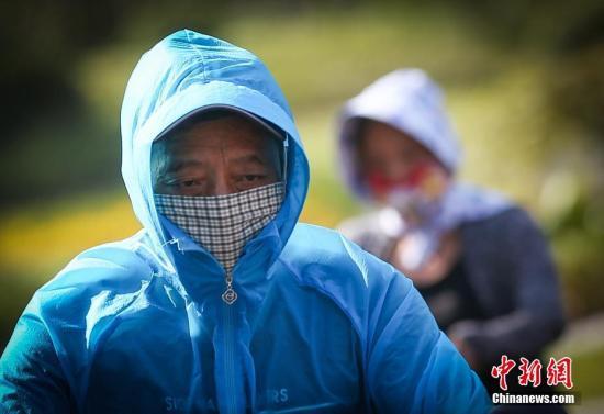 7月24日,将脸部捂得严严实实的市民经过高温下的南京街头。当日,南京市气象台发布高温红色预警信号。中新社记者 泱波 摄