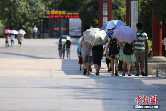 资料图:高温天民众遮阳出行。中新社记者 张远 摄