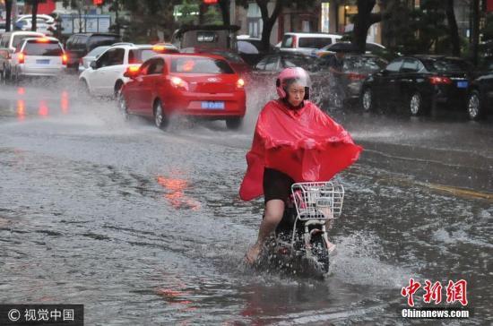 7月24日,青岛市出现遇短时强降雨,积水路段成河流,市民在雨中出行。王海滨 摄 图片来源:视觉中国