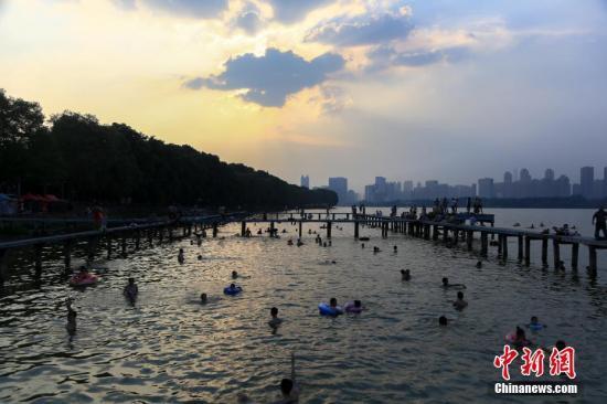7月25日,武汉东湖凌波门露天泳池内,众多市民在此戏水纳凉。当日,武汉中心气象台发布高温红色预警。武汉、十堰、襄阳等9个地市高温突破40℃。未来三天,湖北省大部地区最高气温为37℃到40℃,局部地区最高气温将达到41℃到42℃。 中新社记者 张畅 摄