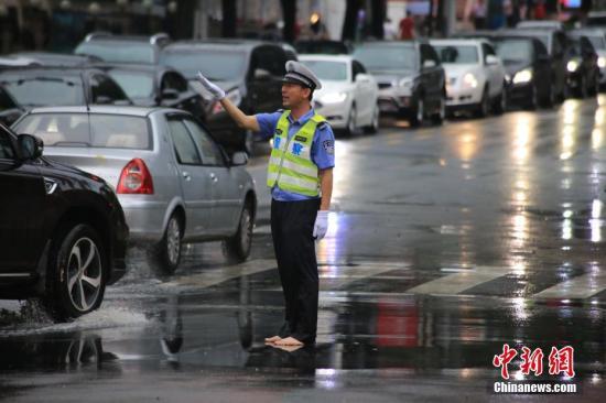 7月24日,青岛市区突降暴雨,造成多条道路拥堵、车流缓慢。一名交警赤脚站在马路中间,指挥过往车辆安全通行。 中新社发 冯浩 摄 图片来源:CNSPHOTO