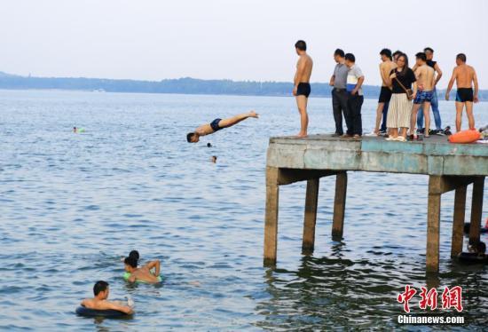 7月25日,武汉东湖凌波门露天泳池内,一位市民从高台上跃入湖中。当日,武汉中心气象台发布高温红色预警。武汉、十堰、襄阳等9个地市高温突破40℃。未来三天,湖北省大部地区最高气温为37℃到40℃,局部地区最高气温将达到41℃到42℃。 中新社记者 张畅 摄